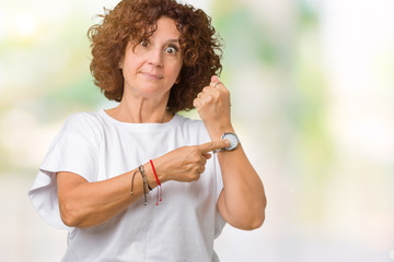 Beautiful middle ager senior woman wearing white t-shirt over isolated background In hurry pointing to watch time, impatience, upset and angry for deadline delay
