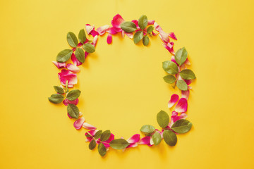 Round frame from pink petals and leaves of roses on a yellow background, top view, copy space. Flower background