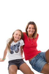Mother and young daughter in an affectionate pose sit on floor on a white background