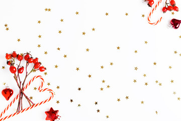 Christmas composition. Red rosehip berries on a white background and golden stars. Christmas, new year, winter concept. Flat lay, top view, copy space