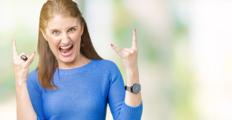 Beautiful middle age mature woman wearing winter sweater over isolated background shouting with crazy expression doing rock symbol with hands up. Music star. Heavy concept.