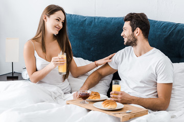 young smiling couple having breakfast in bed