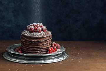 Powdered Sugar Falling on to Stack of Dark Chocolate Pancakes Topped with Raspberries and Red Currants