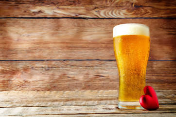 Glass of cold light beer with heart on a wood background for Valentine's day