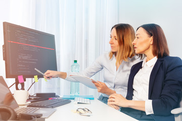 Two businesswomen working with computer in office
