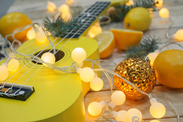 Photo of yellow ukulele, lemons and fir tree branches on wooden background.