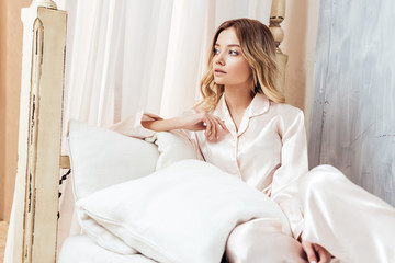 thoughtful blonde girl in pajama sitting in bed during morning time at home