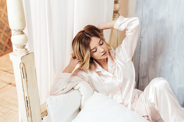 high angle view of young woman in pajama sitting in bed during morning time at home