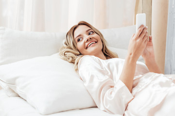 joyful beautiful girl using smartphone in bed during morning time at home