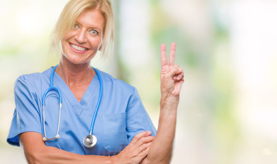Middle age blonde nurse surgeon doctor woman over isolated background smiling with happy face winking at the camera doing victory sign. Number two.
