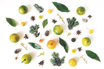 Christmas styled composition. Tangerine citrus fruit and leaves, fir tree branches, anise stars, holly berries and little apples on white table background. Winter holiday pattern. Flat lay, top view.