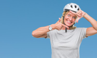 Middle age caucasian cyclist woman wearing safety helmet over isolated background smiling making frame with hands and fingers with happy face. Creativity and photography concept.