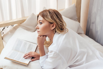 pensive girl in pajama reading book in bed during morning time at home