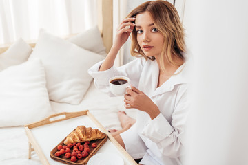 selective focus of young woman holding coffee cup while sitting on bed with breakfast on tray