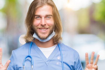 Young handsome doctor man with long hair over isolated background showing and pointing up with fingers number eight while smiling confident and happy.