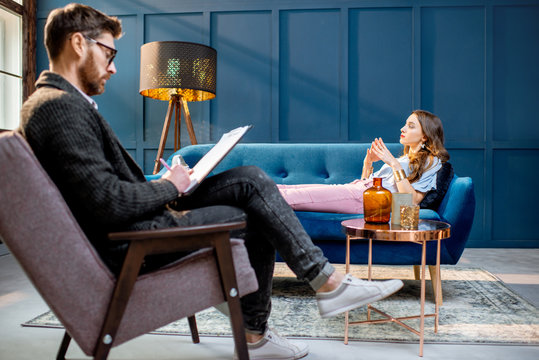 Young woman visiting male psychologist lying on the comfortable couch during psychological session in the luxury blue office interior