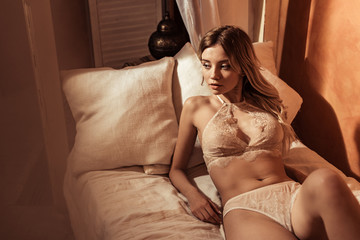 selective focus of female model wearing sexy beige lingerie and posing in bed