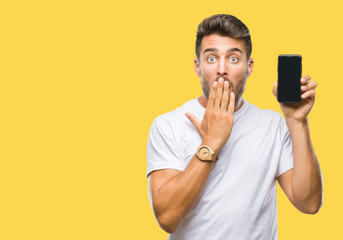 Young handsome man showing smartphone screen over isolated background cover mouth with hand shocked with shame for mistake, expression of fear, scared in silence, secret concept Wall mural