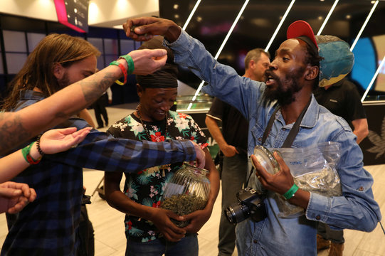 Cannabis activist Steven Thapelo Khundu hands out cannabis buds from a plastic bag at the expo entrance, encouraging attendees to bring them inside, during the opening of the four-day expo in Pretoria