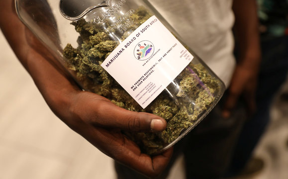 A man holds a jar full of cannabis buds before they were handed out by activist Steven Thapelo Khundu at the expo entrance, encouraging attendees to bring them inside, during the opening of the four-day expo in Pretoria