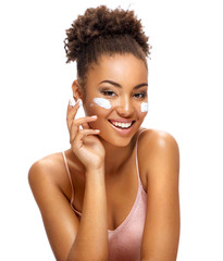 Аttractive girl applying moisturizing cream. Photo of smiling african american girl with healthy skin on white background. Skin care and beauty concept