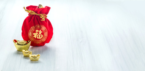 Chinese new year decoration,red fabric packet or ang pow with chinese style pattern and golden ingots on wood table top, Chinese Language mean Happiness,Leave space for add text