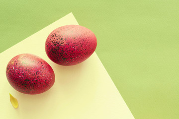 Red Easter eggs on a green paper, top view, copy space
