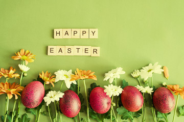 Red Easter eggs and flowers of a chrysanthemum on a green background, top view