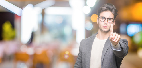 Young business man wearing glasses over isolated background Pointing with finger up and angry expression
