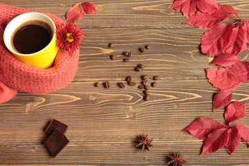 Кофе в желтой кружке, красные листья, цветок и шоколад на деревянном столе.