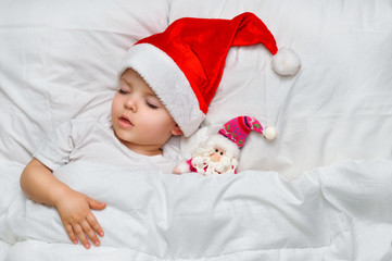 Little baby sleeping on white linen in the Santa hat with his toy Santa Claus.