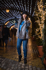 Pretty dark haired girl wearing a fur coat, blue jeans, blue top and a black hat, smiling, posing with snowflakes Christmas lights outdoor at night time.