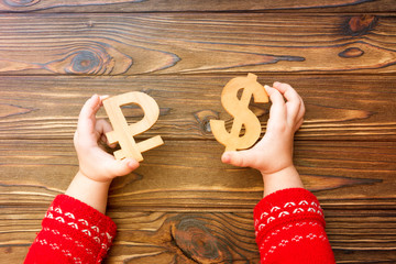 the symbol of the ruble, the dollar in his hands on a wooden background. Finance, currency, cash.