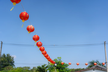 shot of arrangement decoration Chinese new year & lunar new year holiday background concept.China lantern hanging on beautiful blue sky on outdoor.Other language mean rich or wealthy and happy.
