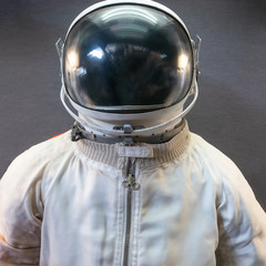 White astronaut or spaceman suit and helmet on grey background