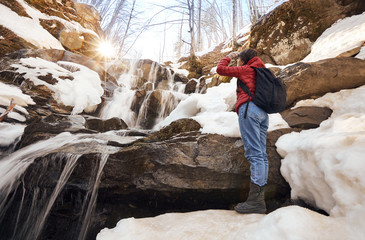 Girl looking at winter waterfall and orange sun