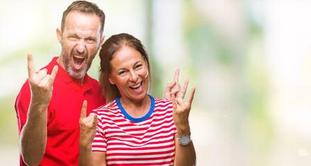 Middle age hispanic couple in love over isolated background shouting with crazy expression doing rock symbol with hands up. Music star. Heavy concept.
