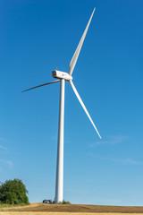 Grande éolienne avec des techniciens à son pied sur fond de ciel bleu