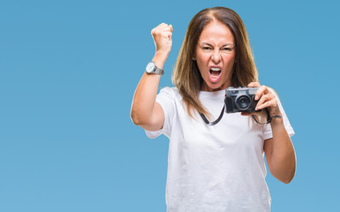 Middle age hispanic woman taking pictures using vintage photo camera over isolated background annoyed and frustrated shouting with anger, crazy and yelling with raised hand, anger concept