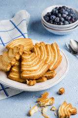 Delicious puff pastry cookies, and blueberries on delicate blue background.