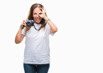 Middle age hispanic woman taking pictures using vintage photo camera over isolated background with happy face smiling doing ok sign with hand on eye looking through fingers
