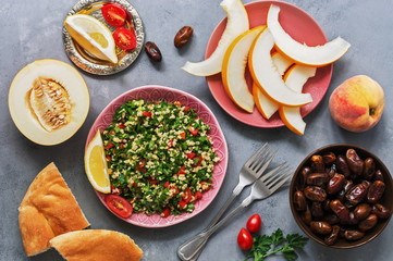 Middle Eastern and Arab food tabbouleh salad, pita, melon, peach and dates on a gray background. Top view, flat lay.