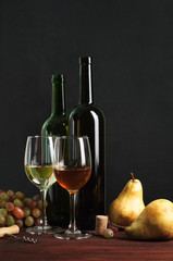 Wine in bottles and glasses on a brown wooden board. The dark background. Next to the  grapes. Author's retouching.