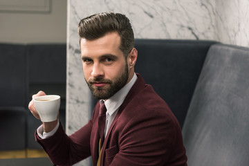 handsome businessman in formal wear looking at camera, sitting at table and drinking coffee in restaurant
