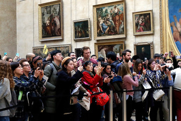 """Visitors take pictures of the painting """"Mona Lisa"""" by Leonardo Da Vinci at the Louvre museum in Paris"""