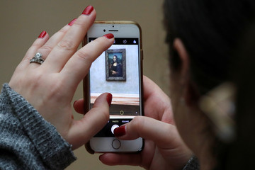 """A visitor takes a picture of the painting """"Mona Lisa"""" by Leonardo Da Vinci at the Louvre museum in Paris"""