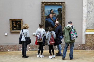 "Visitors look at the painting "" The Virgin and Child with Saint Anne "" by Leonardo Da Vinci at the Louvre museum in Paris"