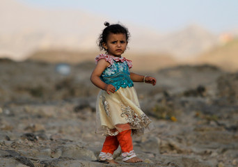 A girl walks near her house destroyed in an air strike carried out by the Saudi-led coalition in Faj Attan village, Sanaa