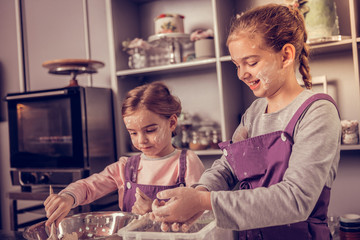 Positive young girls cooking together in the kitchen