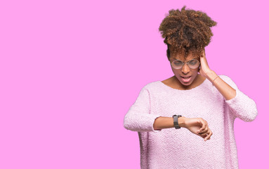 Beautiful young african american woman wearing glasses over isolated background Looking at the watch time worried, afraid of getting late